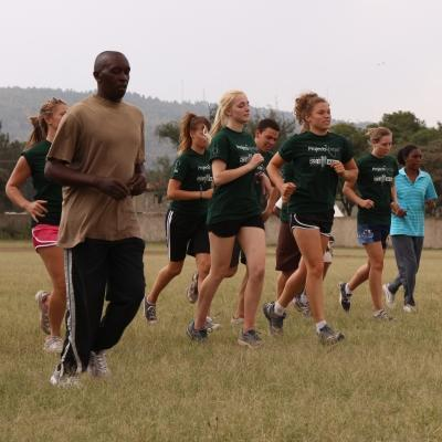 Sports enthusiasts jog to warm up during their volunteer sports coaching in Kenya